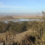 View of lake Elementaita, Kenya and flamingo flocks. The Lord's nose hill in middle background